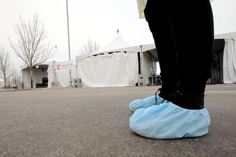 Person wearing shoe coverings outside hospital